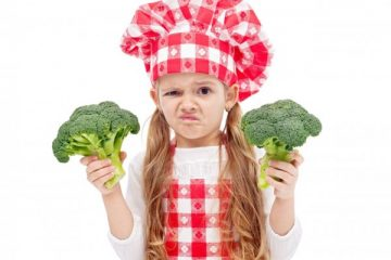 Broccoli again - child with chef hat holding broccoli , isolated